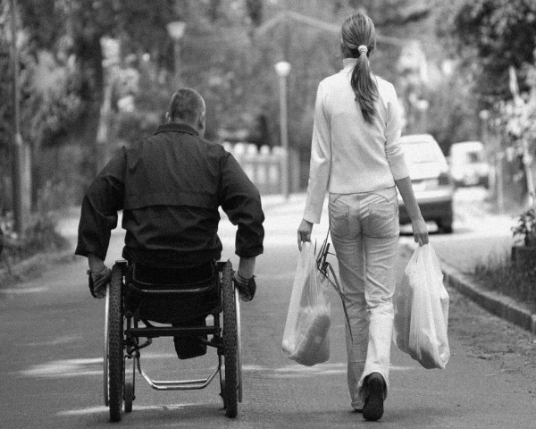 Man on a wheelchair with a woman walking by his side