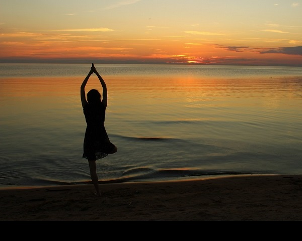 Silhouette of a girl doing yoga near seashore