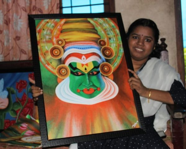 sajitha wheelchair artist holding painting