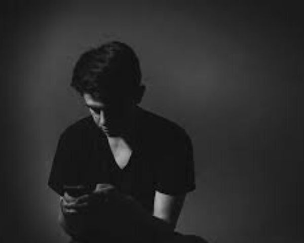 Black and white picture of a boy looking at a mobile phone