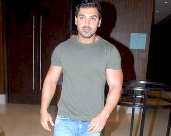 John Abraham wearing blue jeans and grey Tshirt