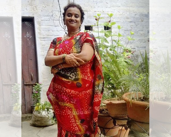 Nalini standing with folded hands in front of some greenery