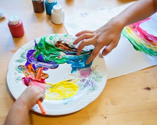 Children's hands hover over a plate of art colours