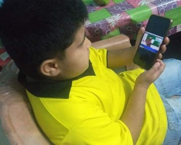 Boy wearing yellow T-shirt watching a video on a mobile phone