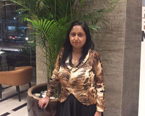 Neetu Wadhwa standing next to a plant