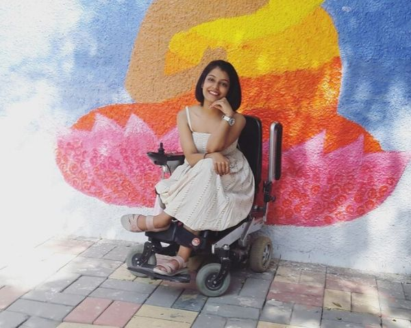 Pratishtha Devsshwar is wearing a white dress and is seated on her wheelchair