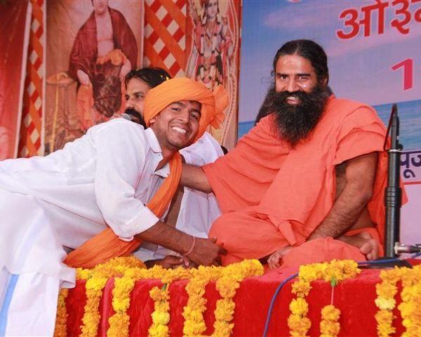 Yoga teacher Ramdev with a disciple
