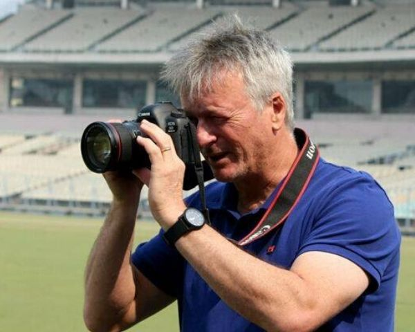 Steve Waugh wearing.a blue Tshirt and holding a camera