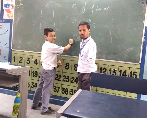 Lalit Sharma standing in a classroom with a student.
