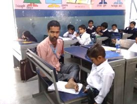 Lalit Sharma is writing with his toes as a student watches.