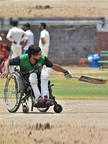 Aditya Chokkhar batting on the field in his wheelchair.