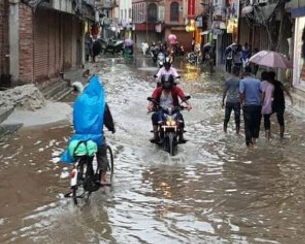 People riding scooters on rain drenched streets