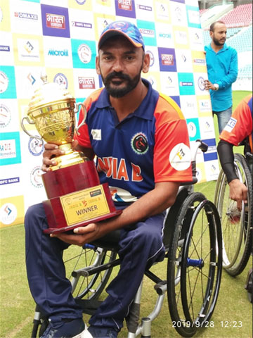 Nirmal Dhillon, wheelchair cricketer holds a trophy.
