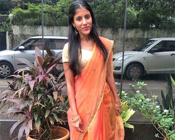 Saakshi Mahnot is wearing an orange saree.