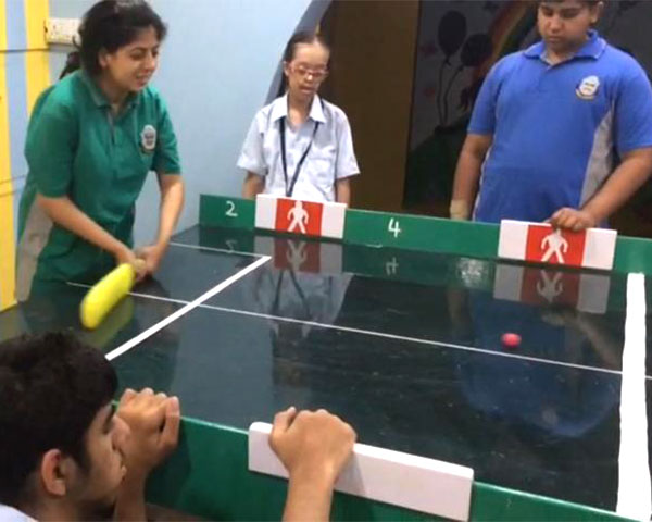 Game of table cricket in progress between students with and without disabilities.