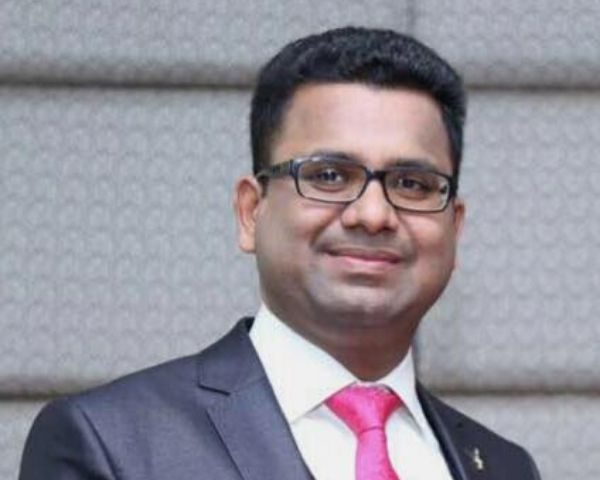 Close up photo of Milan Mittal in a suit and pink tie