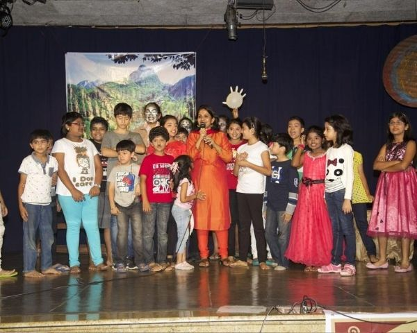 Rachna Prasad standing with.a group of children with disabilities on stage