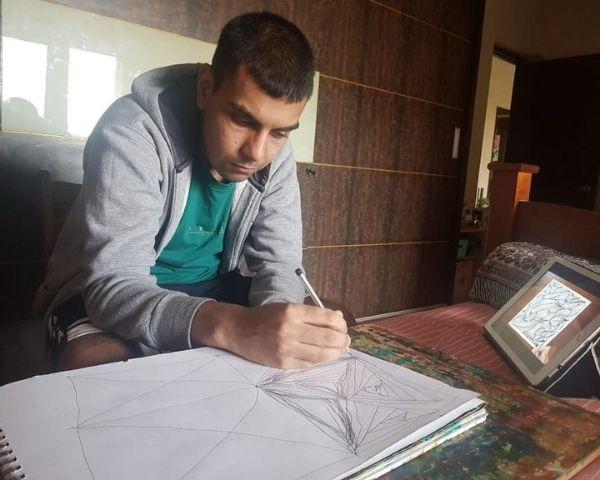 Anshuman Kar is wearing a grey jacket and green T shirt