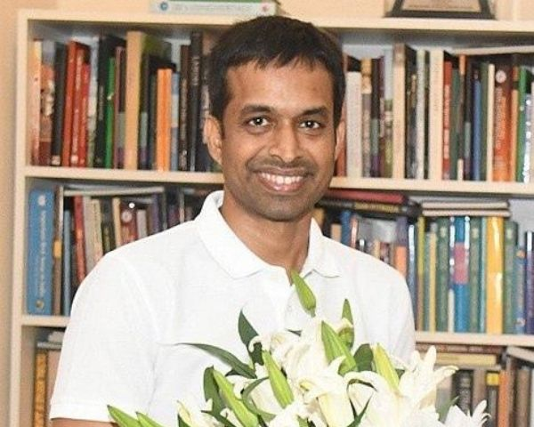 P Gopichand is wearing a white T shirt and holding flowers