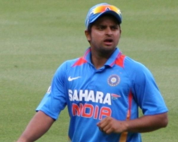 Suresh Raina is wearing a blue T shirt with the words Sahara India