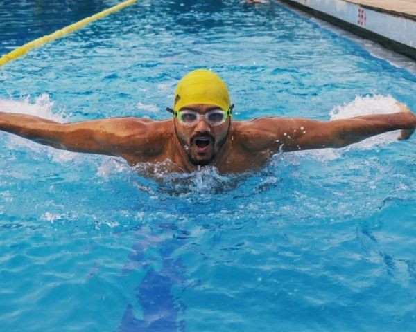 Satendra Singh is swimming in a poll wearing a yellow cap