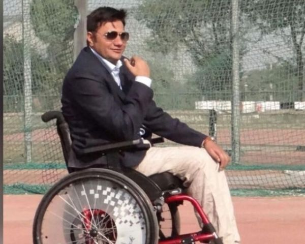 Amit Saroha is wearing a suit and is sitting on a wheelchair