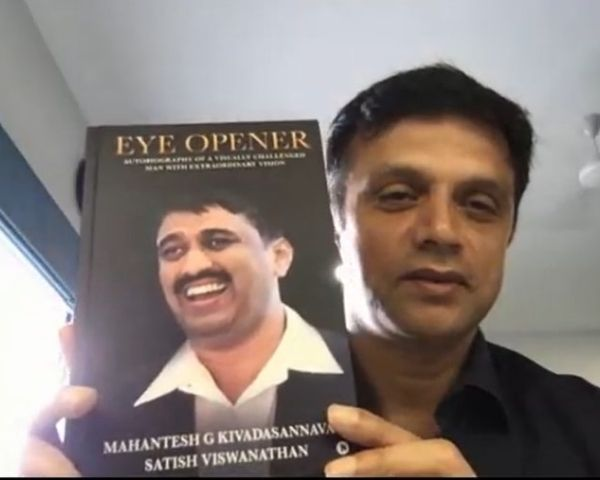 Rahul Dravid is holding a book with the picture of GK Mahantesh