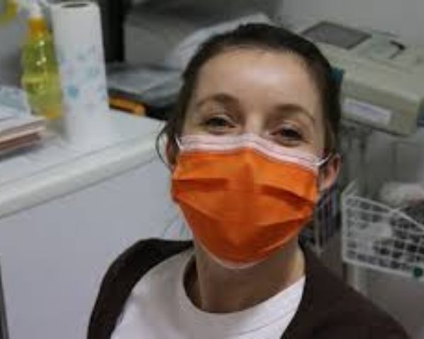Young girl wearing an orange face mask