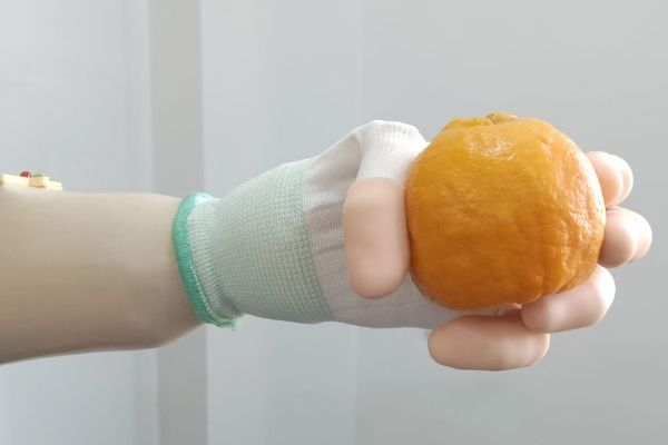 Person using Grippy holding an orange.