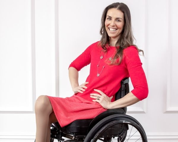 Samanta Buollock is wearing a red dress and seated on a wheelchair