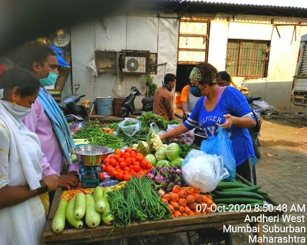 Customers buying vegetables from Bhagat's cart.