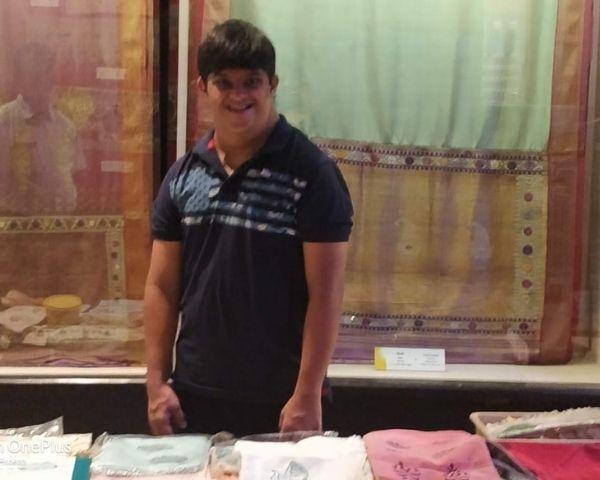 Ameet Kulkarni is wearing a black shirt and smiling