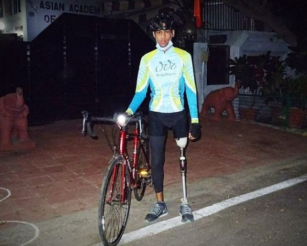 Himanshu Kumar is standing near his cycle