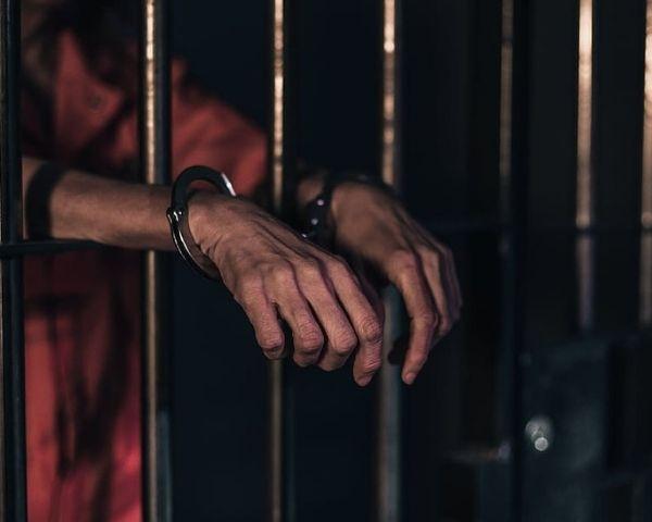 hands of man inside jail