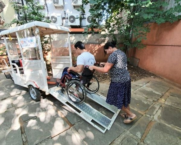 disabled person getting into e rickshaw