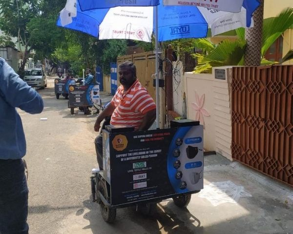 Man sitting on a three wheeler with a box and an umbrella