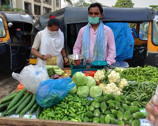 Dhananjay and ANita Bhagat are standing in front of a cart full of vegetablles