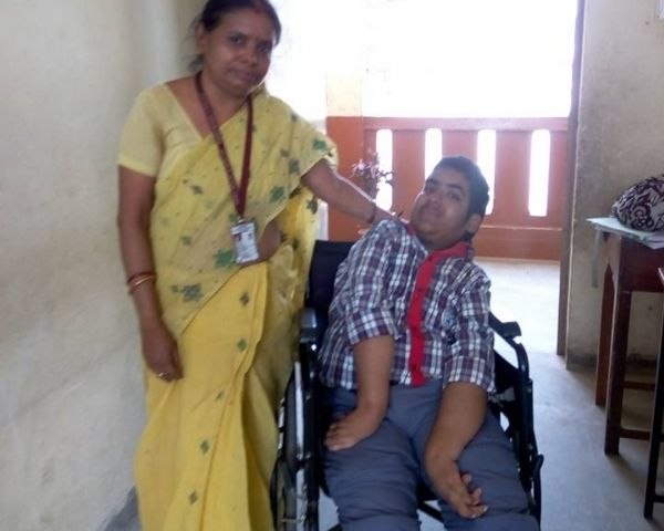 Tuhin Dey in a wheelchair with his mother