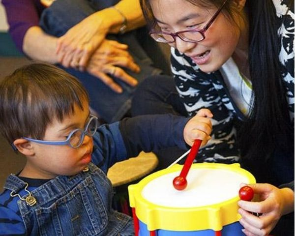 An infant plays with a drum accompanied by a teacher.