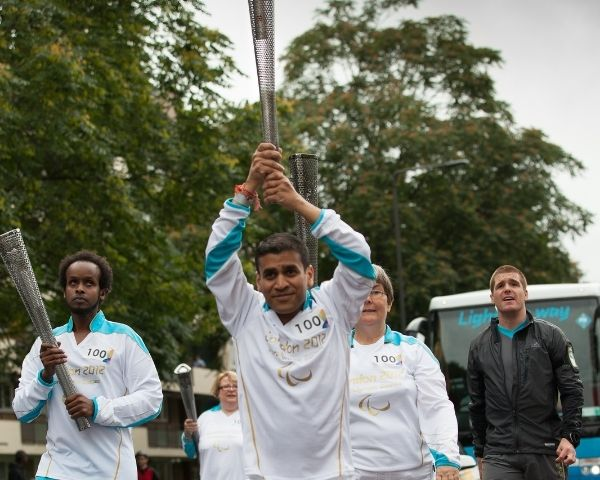 Kush Kanodia carrying the torch at the 2020 London Paralympics