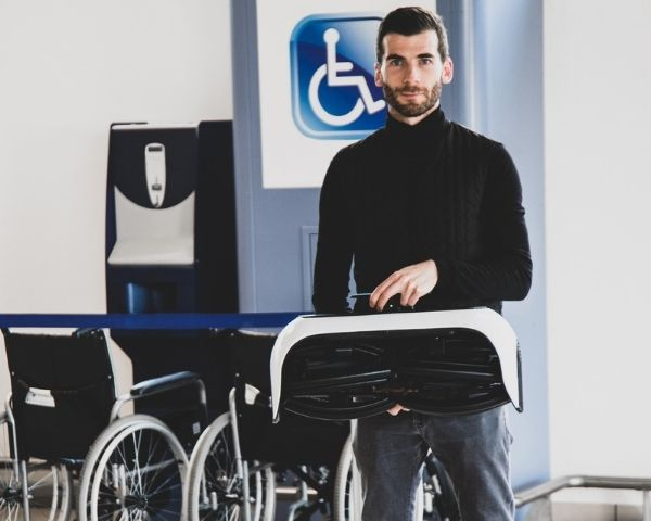 Andrea Mocellin is holding the foldable wheelchair