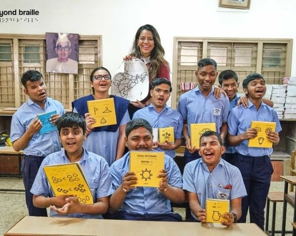 Nupur and blind students at a school in Surat holding a Beyond Braille dictionary