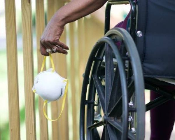 Person in wheelchair holding a Covid mask