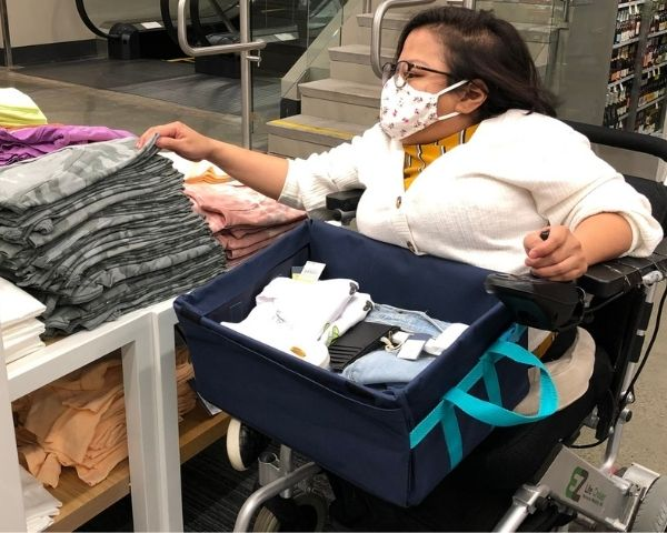 Person in wheelchair shopping with a LapSnap on her lap