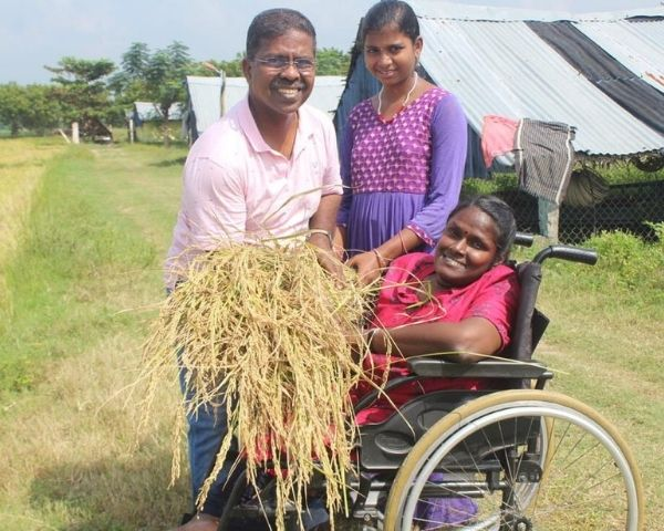 D Indra is sitting on a wheelchair holding paddy accompanied by 2 people