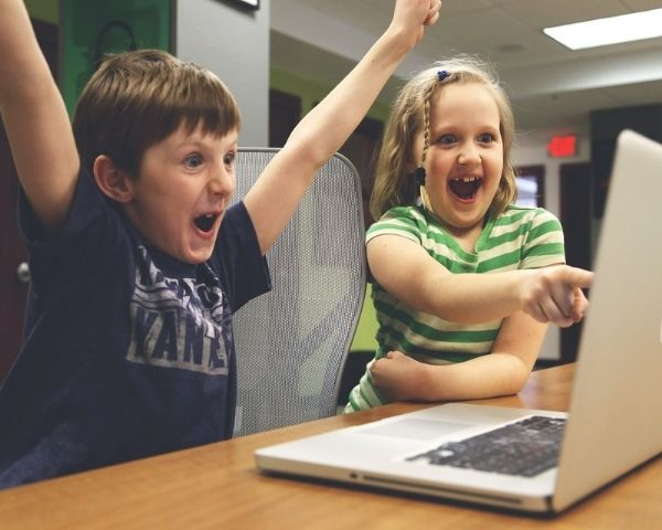 A boy and a girl enjoying a game on a laptop