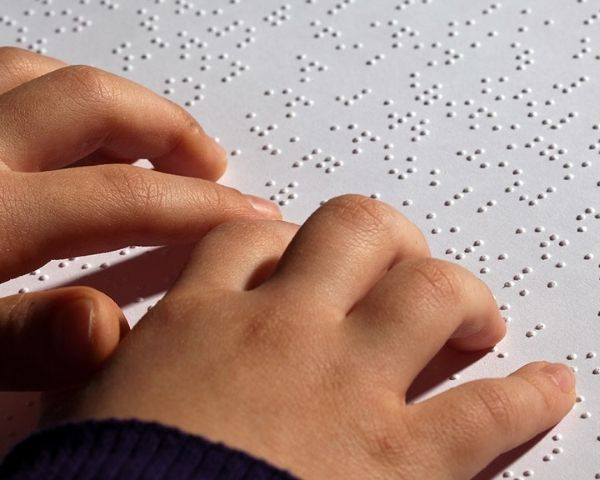 A child's fingers on a Braille sheet