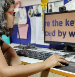 A person with deafblindness operating the computer. The screen on the computer is magnified.